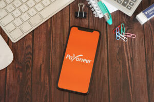 Payoneer App with Stationery on a Brown Wooden Table